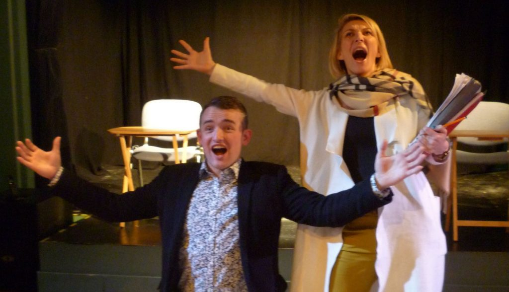 Two performers onstage as part of a play, with their arms raised and mouths open as if they have been making an important announcement